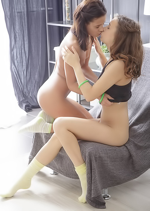 Lesbian chicks share an orgasm in an armchair